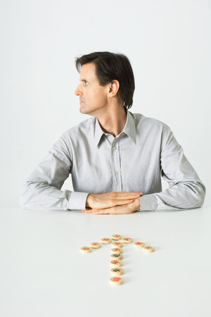 distractions: Man sitting at table, Chinese chess pieces in shape of arrow pointing to him, looking away