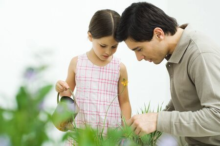 Father and daughter looking down at flower, girl holding watering can