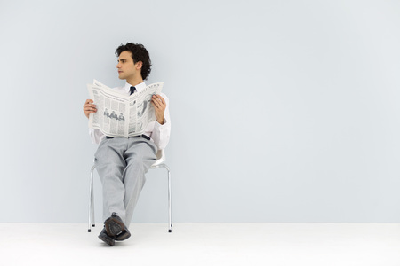 distractions: Businessman sitting in chair, holding newspaper, looking away