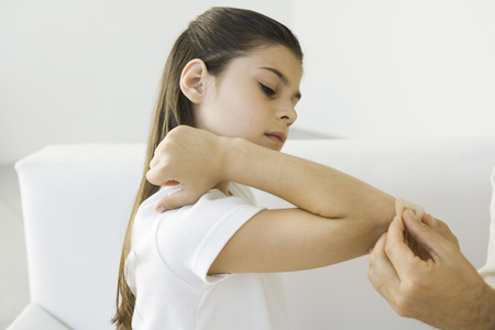 Man putting adhesive bandage on girls elbow, cropped view