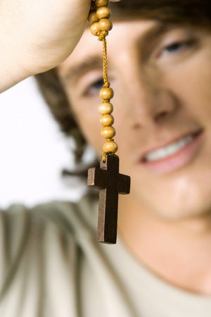 Man holding wooden rosary, focus on foreground LANG_EVOIMAGES
