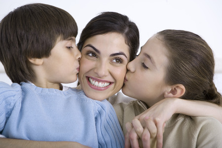 smooching: Portrait of smiling mother being kissed on each cheek by young daughter and son