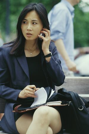 Businesswoman sitting on bench, using cell phone and flipping through agenda