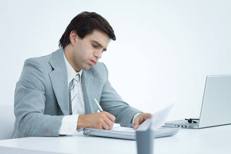 Young businessman working at desk, puffing cheeks