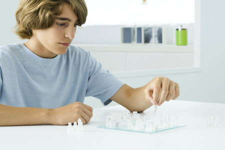 Teen boy sitting at table, playing chess LANG_EVOIMAGES