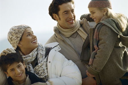 Family outdoors, father carrying daughter, mother ruffling sons hair