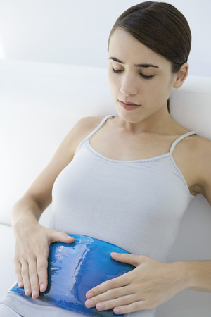 Woman holding compress on stomach, looking down