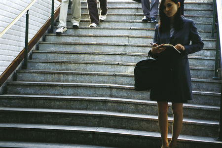 Businesswoman standing at bottom of steps, holding open agenda LANG_EVOIMAGES
