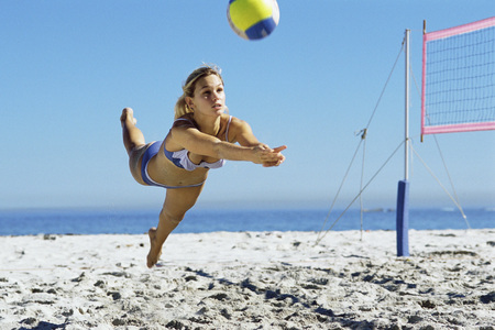 game over: Female playing beach volleyball, diving to catch ball