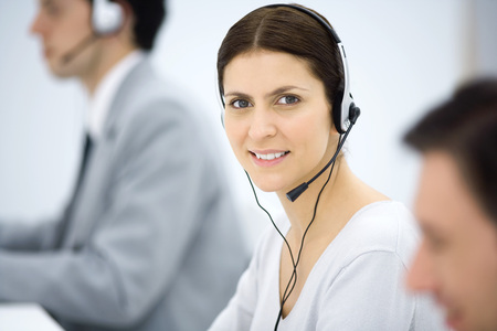 Female telemarketer smiling at camera, portrait
