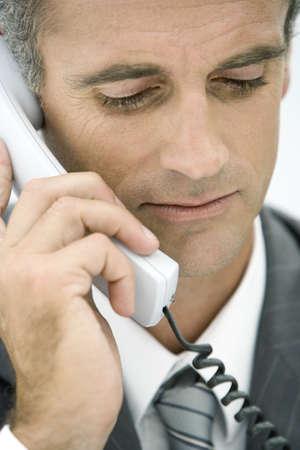 Businessman talking on landline phone, looking down LANG_EVOIMAGES