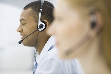 Telemarketers wearing headsets, profile, focus on background