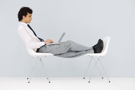 Businessman sitting in chair, feet up on another chair, using laptop
