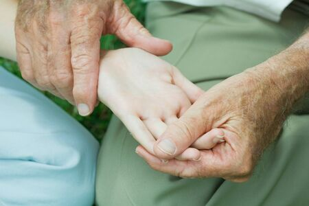 Elderly person holding hand of young person, examining palm
