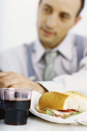 Businessman focusing on work, lunch in foreground