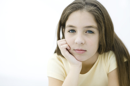 Preteen girl resting chin on hand, portrait