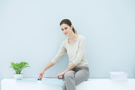 Professional woman sitting on ledge, organizing documents, smiling at camera LANG_EVOIMAGES