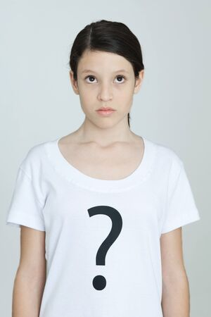 puzzlement: Preteen girl wearing tee-shirt printed with question mark, looking up, portrait
