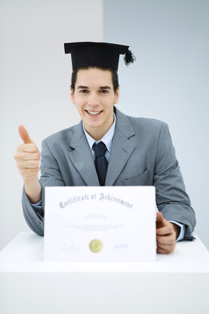 Young man with diploma, wearing graduation cap, making thumbs-up gesture