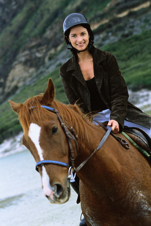 Woman riding horse on beach, portrait