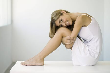 Woman in slip sitting on table, hugging knees, smiling at camera LANG_EVOIMAGES