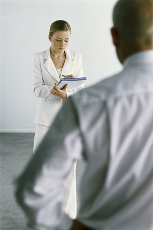 authoritative woman: Young assistant standing taking notes, boss dictating in foreground LANG_EVOIMAGES