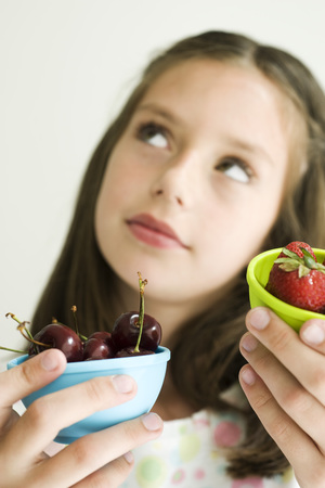 Girl deciding between bowl of cherries and bowl of strawberries