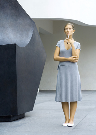 Woman standing next to sculpture, holding pen to chin, full length