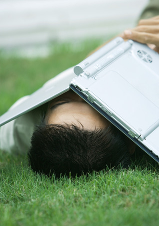 Man lying in grass with laptop covering face