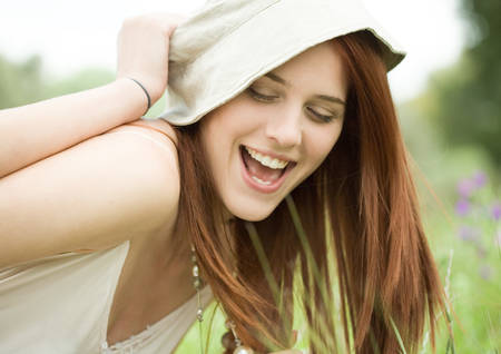 Young woman having hat pulled off