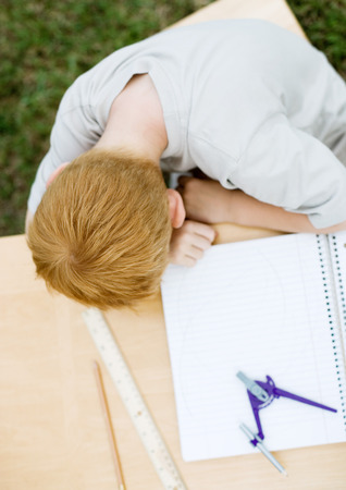 Boy with head on table next to open notebook LANG_EVOIMAGES