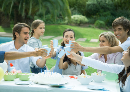 Family clinking cups over birthday cake LANG_EVOIMAGES