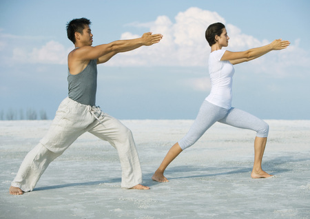 Man and woman stretching on beach