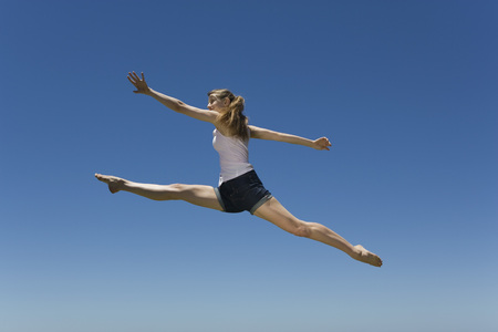 Young woman leaping, midair LANG_EVOIMAGES