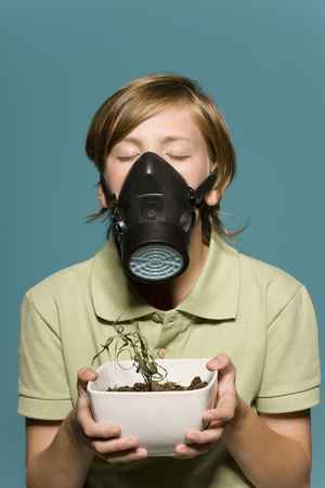 air dried: Boy wearing gas mask, holding wilted potted plant