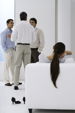 Woman relaxing in arm chair while male colleagues chat in background