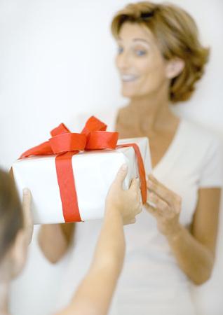 generosidad: Child handing woman gift