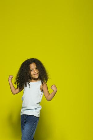 Little girl flexing muscles, portrait