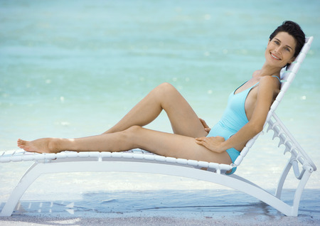 Woman reclining in lounge chair on beach
