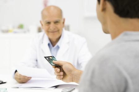 Patient handing credit card to doctor