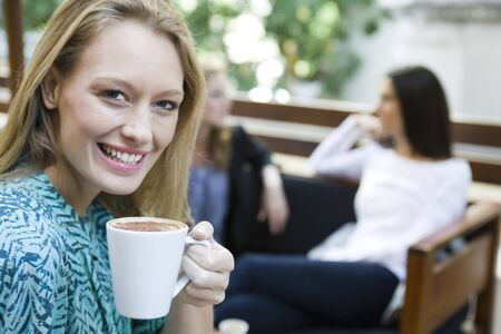 Young woman enjoying cup of coffee, portrait