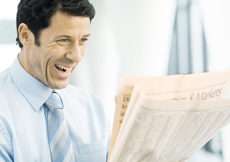Businessman looking at newspaper excitedly