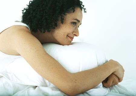 Woman resting head on pillow, smiling