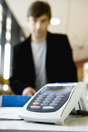 Credit card reader on checkout counter, customer in background