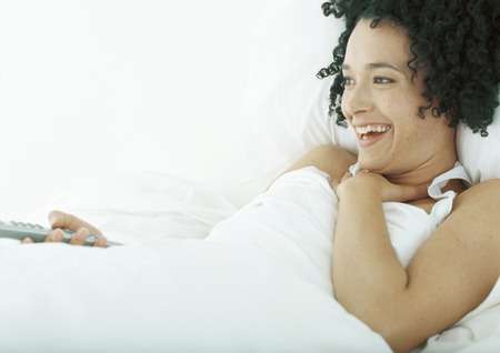Woman lying in bed, holding remote control