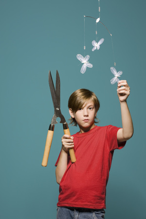 Boy standing below butterfly mobile, holding hedge clippers LANG_EVOIMAGES