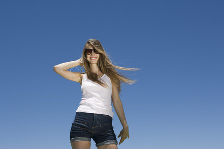 Fashionable young woman in summer apparel with hand in hair LANG_EVOIMAGES