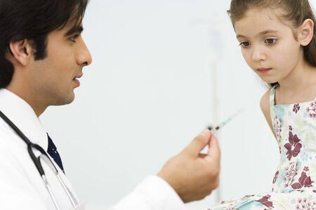 Pediatrician showing little girl syringe