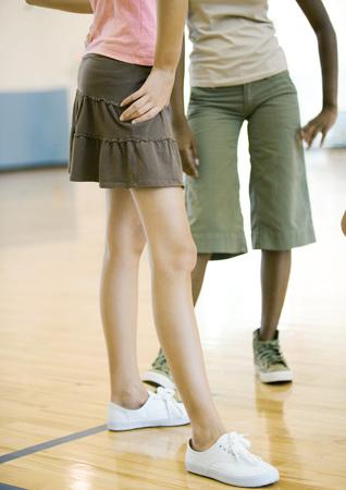 Teen girls standing in gym, waist down