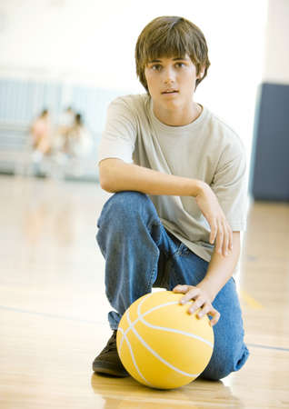 Teen boy crouching with basketball in school gym LANG_EVOIMAGES
